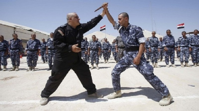 American police advisor (dressed in black) who is a self-defense expert trains a group of Iraqi police recruits.
