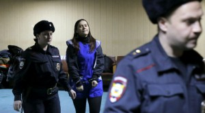 Russian police officers escort suspected jihadist who beheaded a child in Moscow.