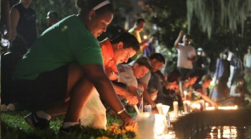 Wendy Frias, from left, and Hector Silva light candles along Lake Eola in Orlando, Sunday, June 12, 2016. The New York natives have made Orlando their home in recent years and came to the vigil for the victims of the Pulse night club tragedy. (AP)
