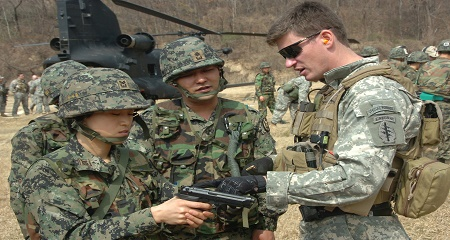 U.S. special forces member helps train South Korean military members.