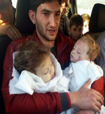Syrian father cradles the bodies of his two children who suffered the effects of sarin gas.