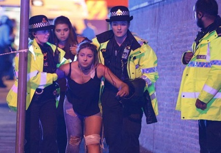Manchester cops assist bomb victim out of the arena.